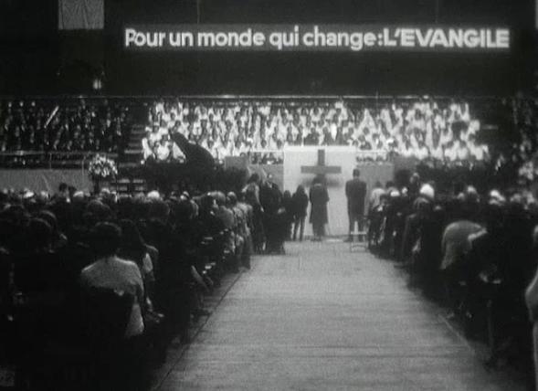 Dans la salle de Genève où se déroulait la campagne d'évangélisation de Leighton Ford en 1966. L'image est extraite du reportage 1966 ans après Jésus-Christ, qu'on peut visionner sur le site des archives de la Radio Télévision Suisse.